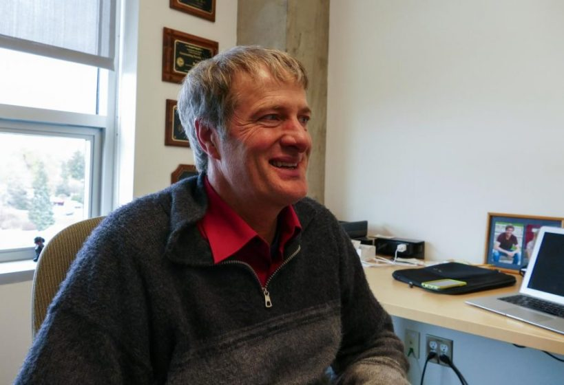 White man with blonde hair and a grey sweater with a red polo underneath half-smiling in an office.