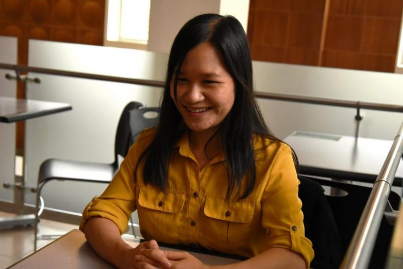 Asian woman in yellow button down shirt sitting at a table smiling.